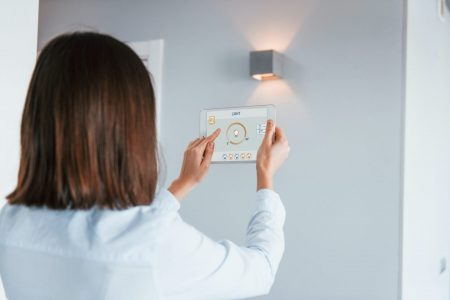 rear-view-of-woman-that-is-indoors-controlling-smart-home-technology.jpg